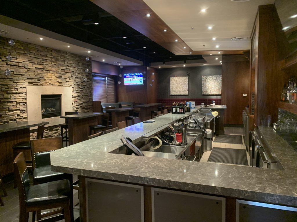 Multiple mounted televisions and installed lights in a restaurant and bar
