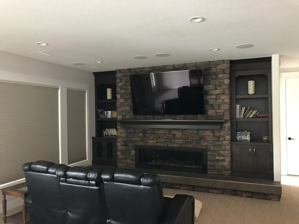 Mounted tv above a fireplace and cozy seating arrangment