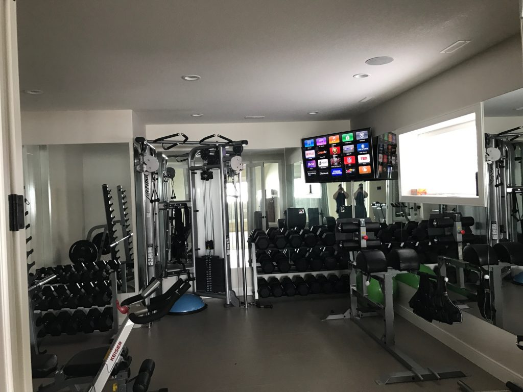 mounted tv in the corner of a home gym with a ceiling speaker
