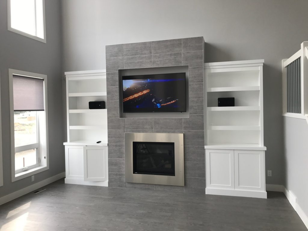 mounted television above a chrome fireplace in a bright room